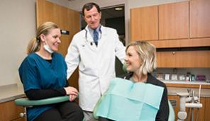 Dentist and dental hygienist with patient